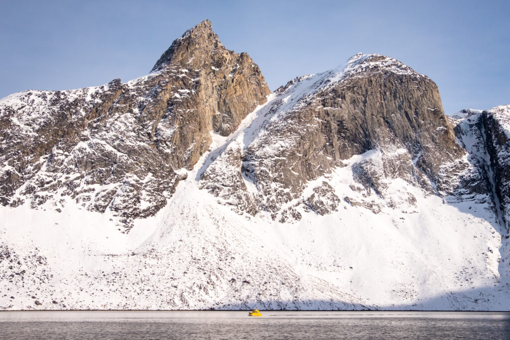 Yellow tour boat against a massive mountain backdrop in the Nuuk Fjord during winter - Greenland