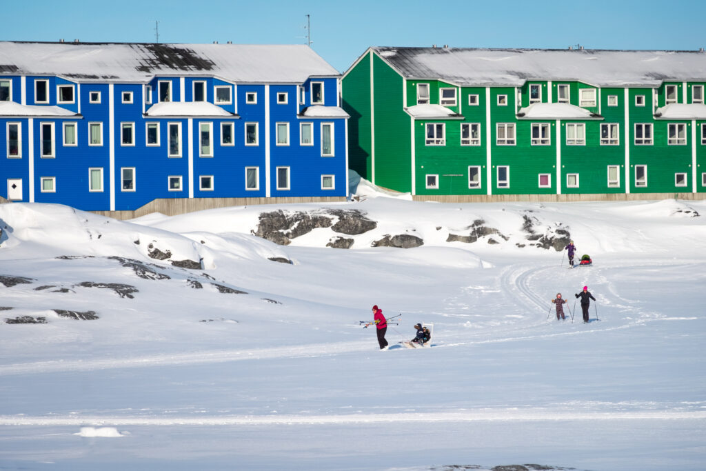 Cross-country skiiers on groomed trails passing the colorful houses in Nuuk's suburb of Nuussuaq - Greenland