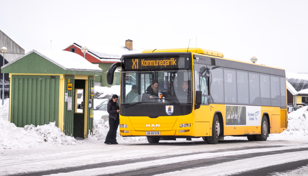 Passengers getting on a bus at a bus stop in Nuuk during winter - Greenland