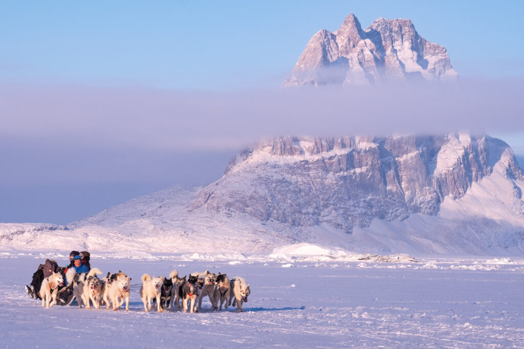 People dogsledding across the sea ice with Uummannaq mountain in the background - Guide to Greenland