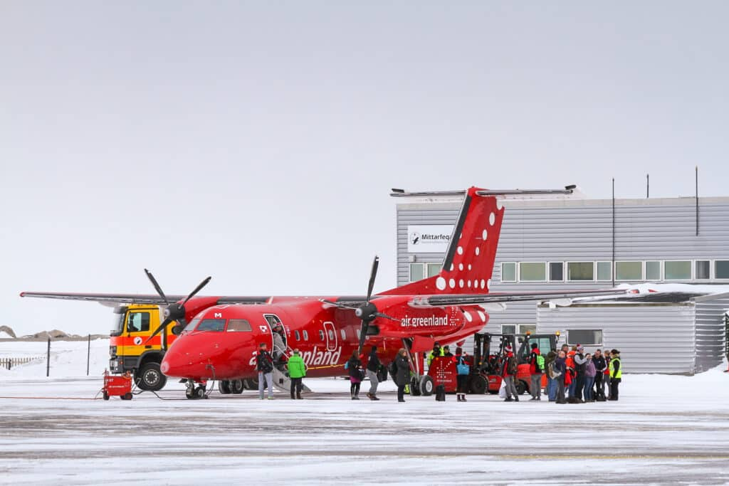 Air Greenland Dash 8 plane and passengers in front of Nuuk airport terminal - Greenland