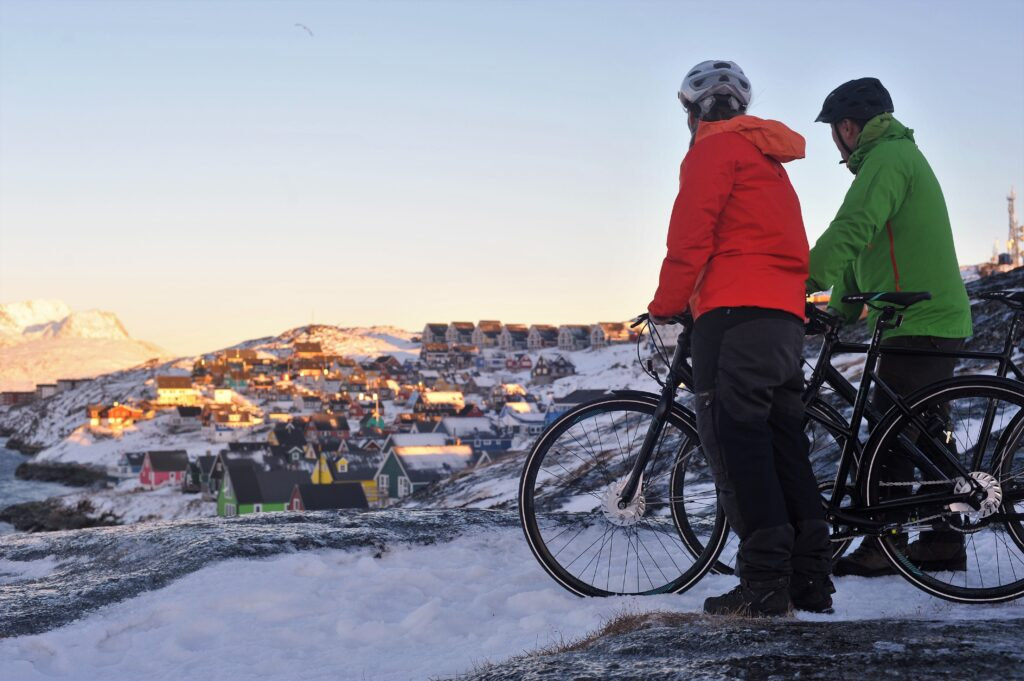 Two people with bikes looking at the view over the Mosquito Valley in Nuuk and Sermitsiaq Mountain - Greenland