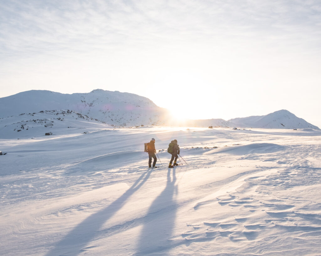 Two people snowshowing near Nuuk are backlit by the low sun - Greenland