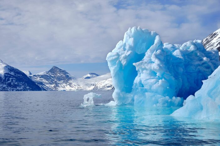 A large iceberg with mountains in the distance on a boat tour up the Nuuk Fjord with Guide to Greenland