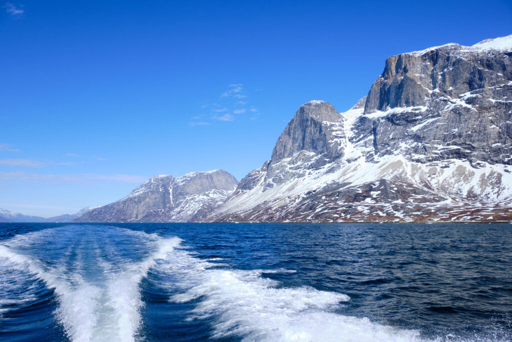 Looking back along the wake of the boat at the impressive mountains of the Nuuk fjord on a boat tour to Qooqqut with Guide to Greenland