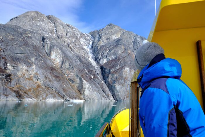 Passenger watches as we approach the mountain at the entrance to the Nuuk Icefjord on a boat tour with Guide to Greenland