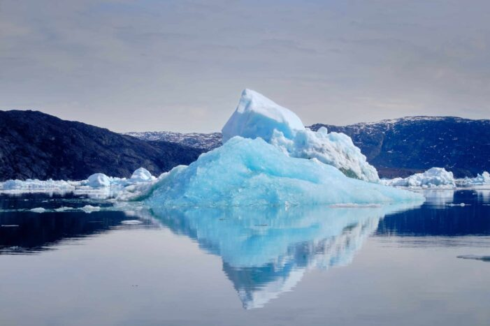 Pyramid iceberg reflected in the water the Nuuk Icefjord on a boat tour with Guide to Greenland