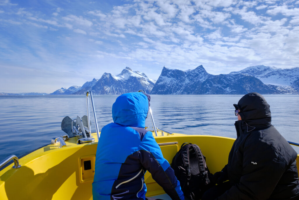 Two passengers sitting on the front deck admiring the mountains of the fjord on a boat tour to the Nuuk Icefjord with Guide to Greenland