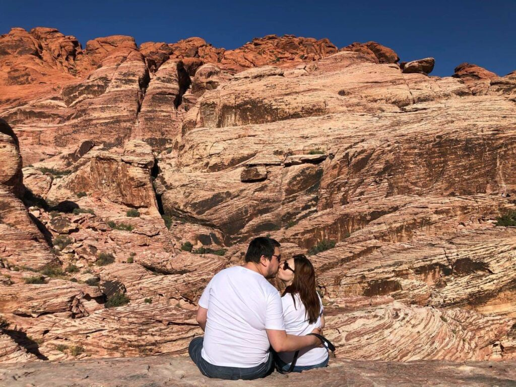 Couple kissing on top of a rock