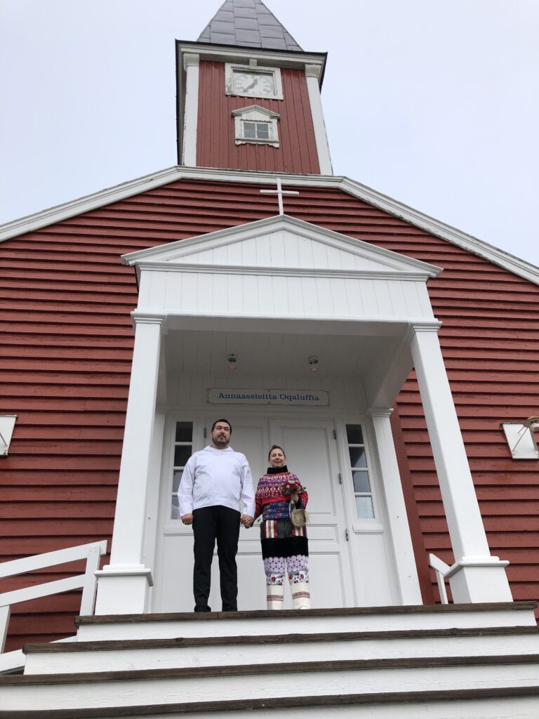 Couple stepping outside after getting married in Greenland