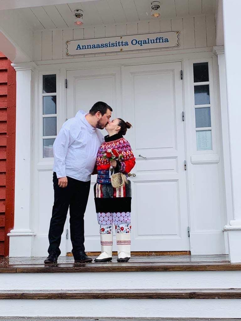 Couple stepping outside and kissing after getting married in Greenland