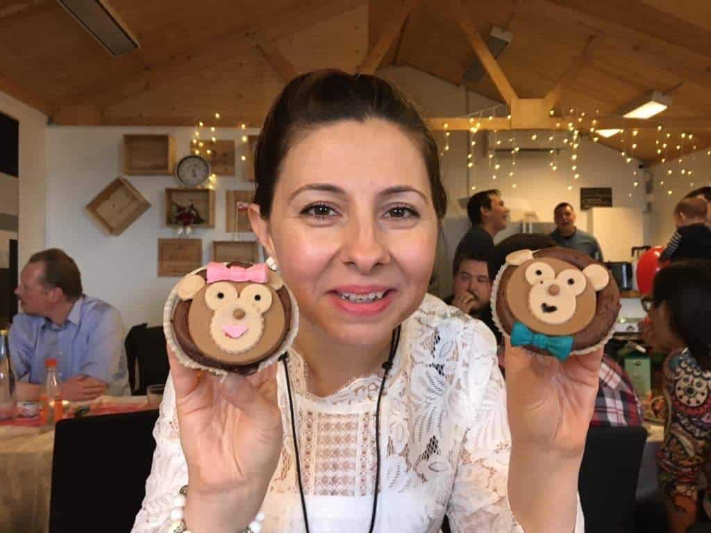 Woman holding up two cupcakes