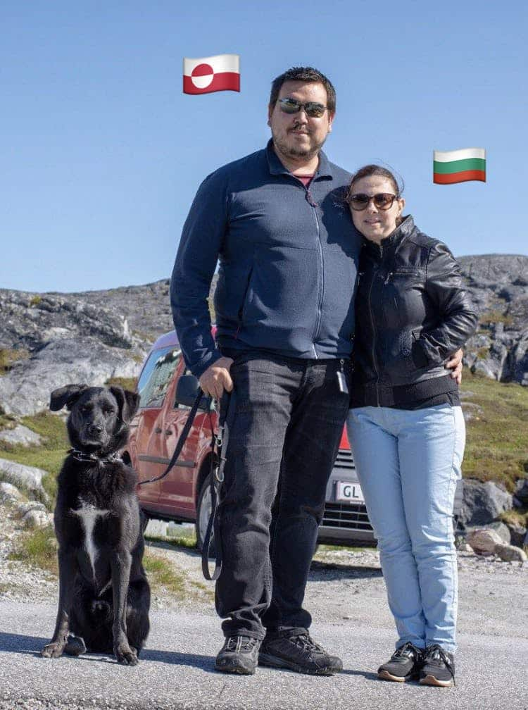 Couple posing with their dog in front of a car