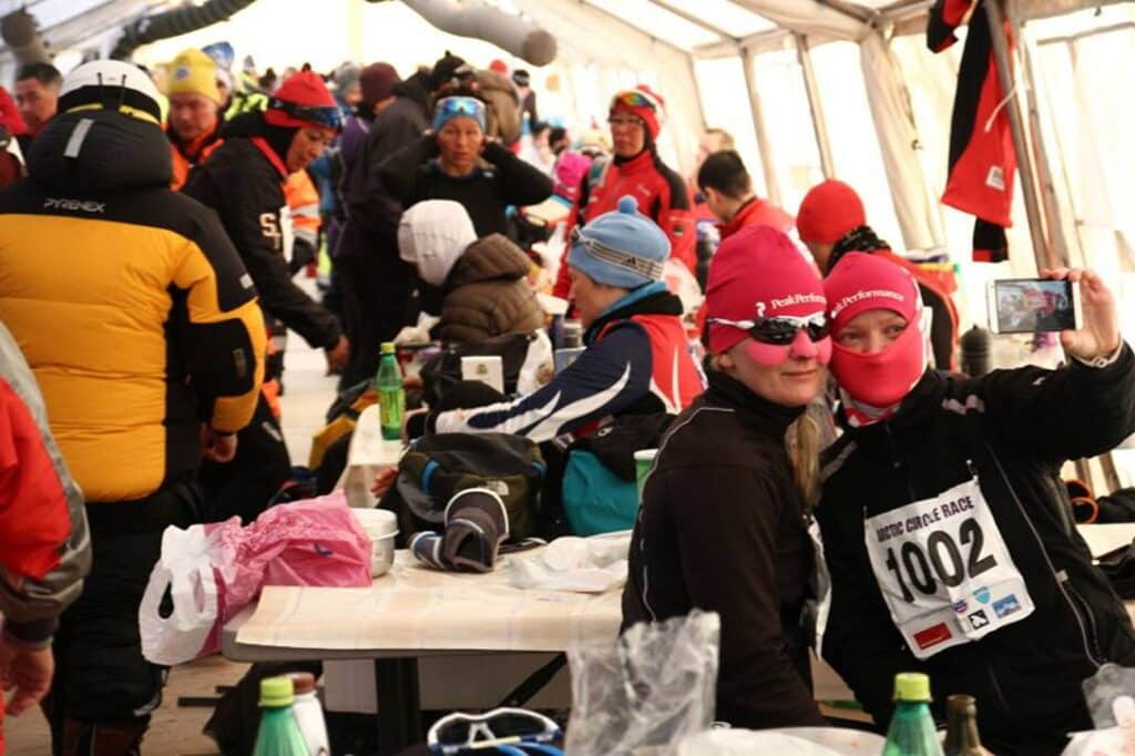 Participants sitting in a large, white tent during Arctic Circle Race
