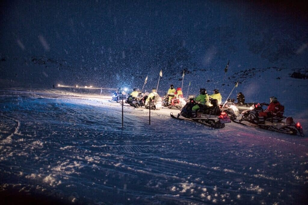 People on snowmobiles during a snowstorm