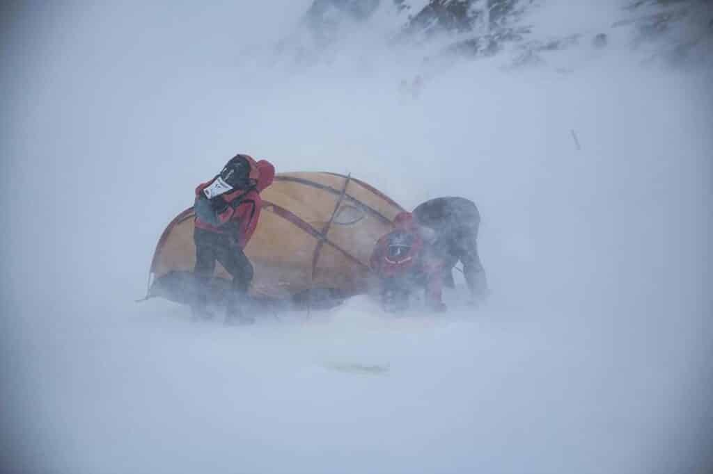 Workers trying to hold down a tent during a snow storm during Arctic Circle Race