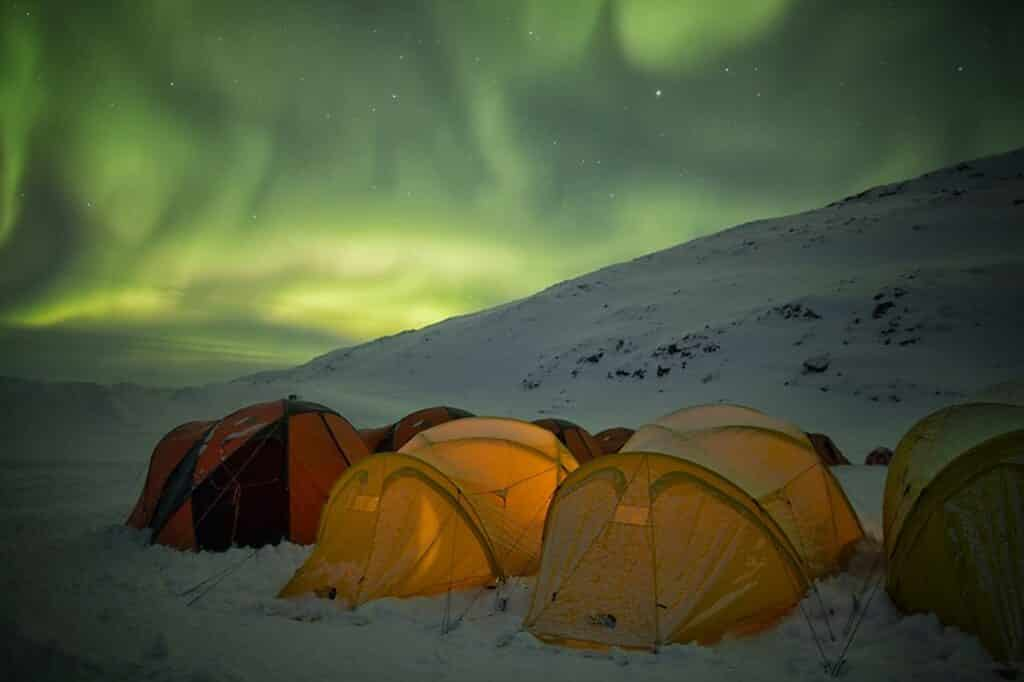 Northern lights over yellow and red tents