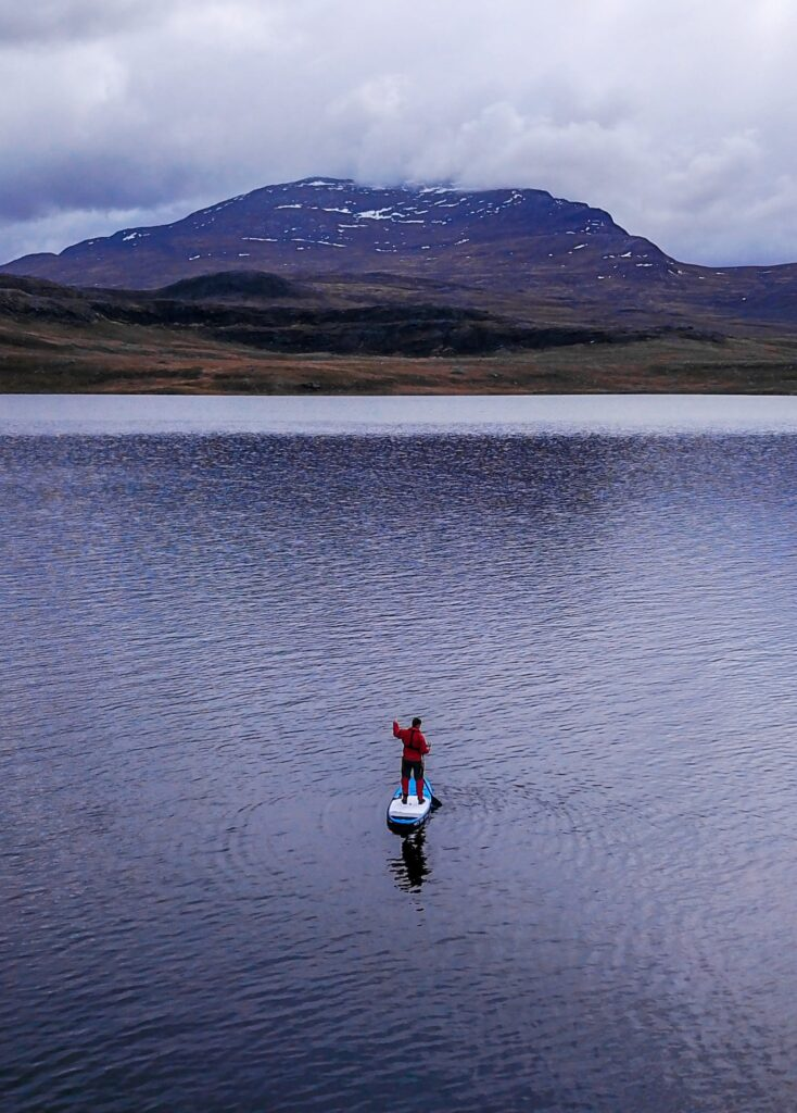 Man in red coat standing on a stand up paddle board in the fjord