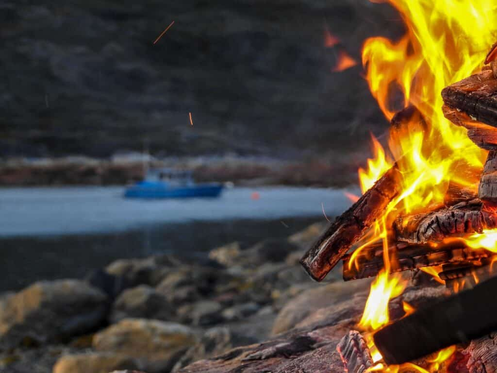 Beach bonfire with a blue boat in the background