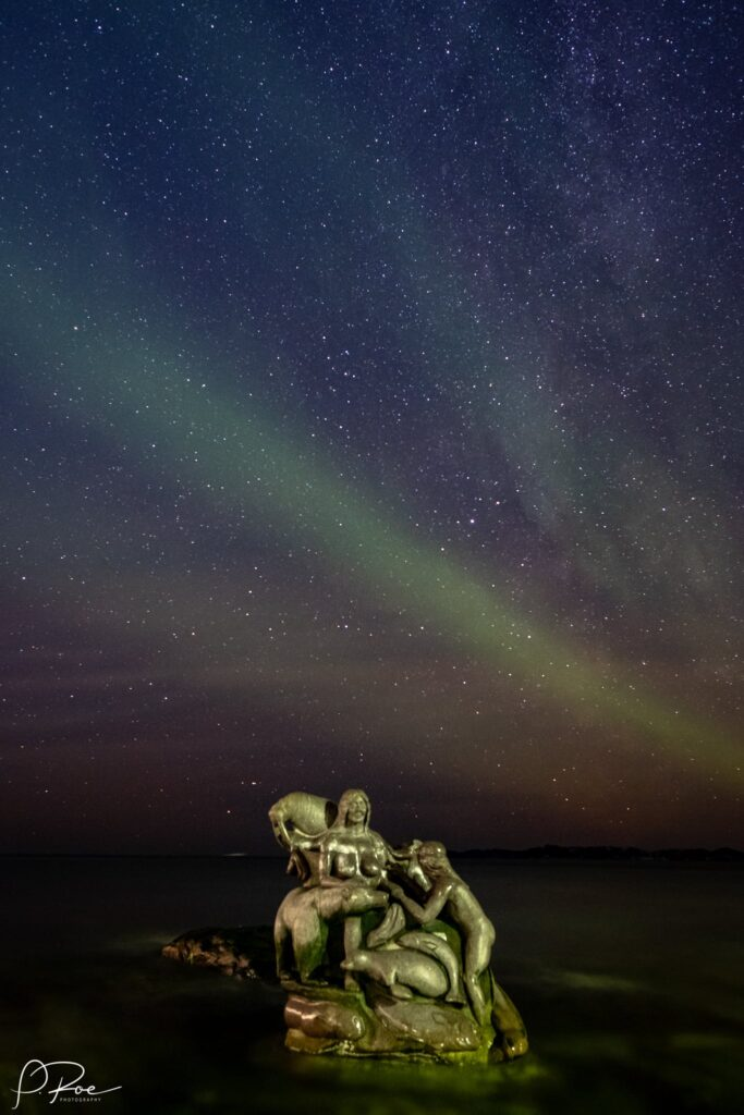 Northern lights over a statue in the water