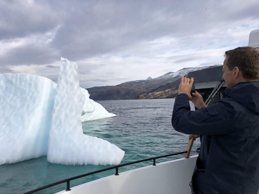 Man taking a picture of an iceberg