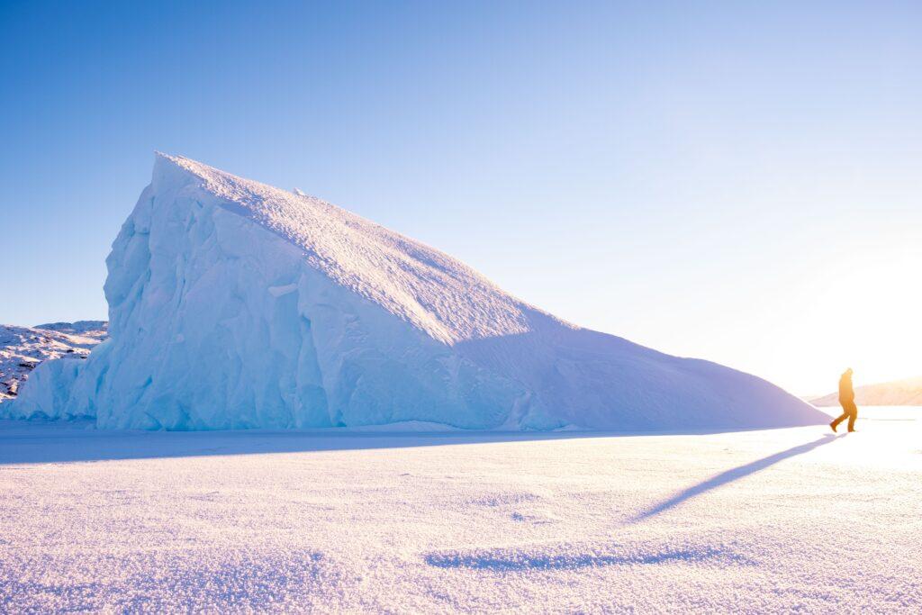 Man walking past a large iceberg