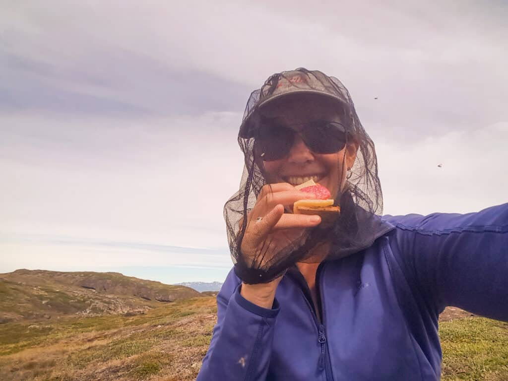 Hiker eating while wearing a head net during a hike in the Summer in Greenland