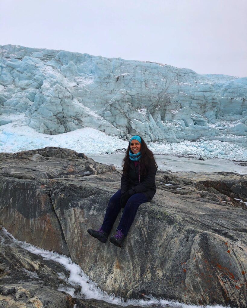 Woman sitting in front of a glacier