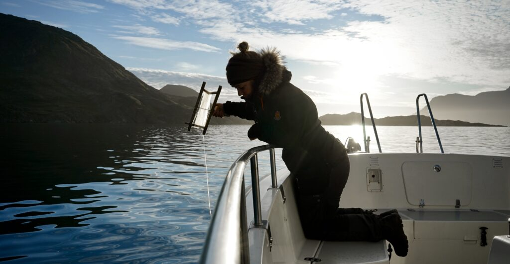 Woman fishing from a boat in Greenland