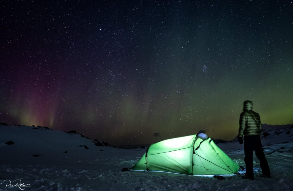 Guys next to a green tent looking at the northern lights