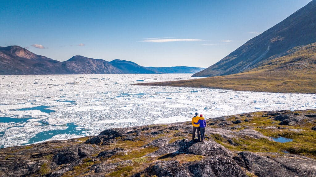 Couple hiking along the Nuuk Fjord filled with chunks of ice