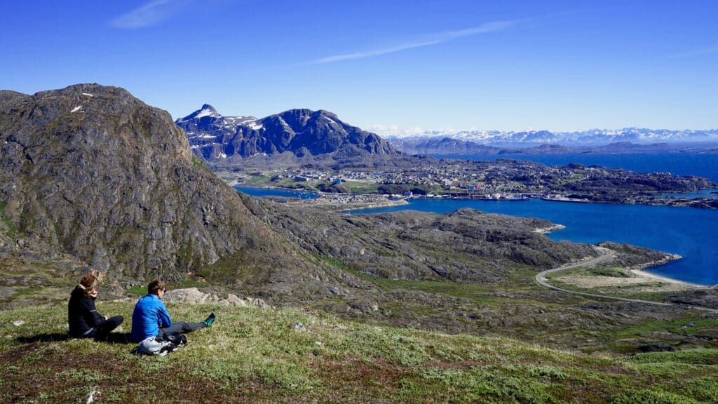 Man and woman looking towards Sisimiut from a mountain top