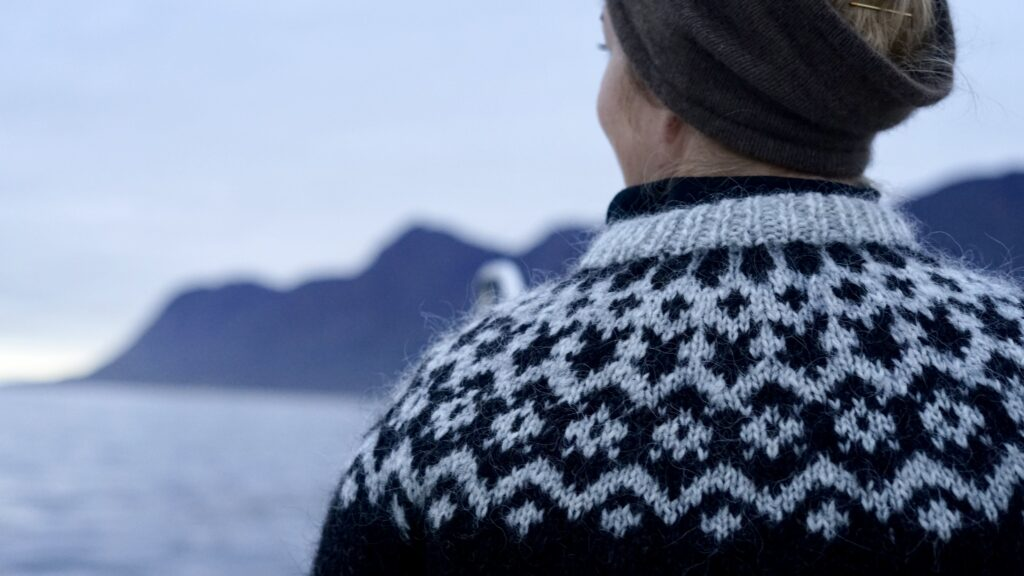 Woman in knit sweater trying to spot seals