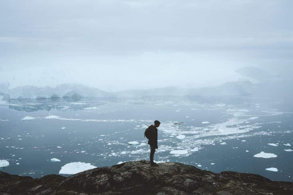 Man looking towards the fiord filled with icebergs