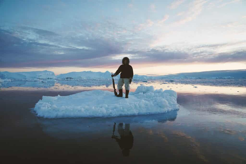Man standing on a block of ice holding a riffle