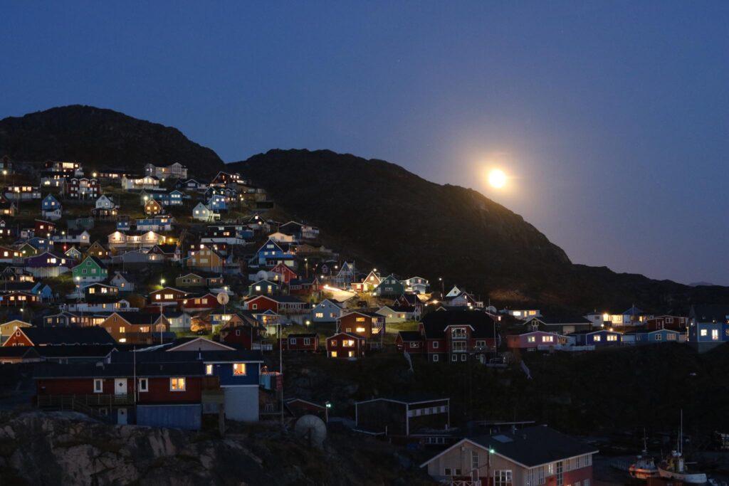Moon over colorful houses in Qaqortoq