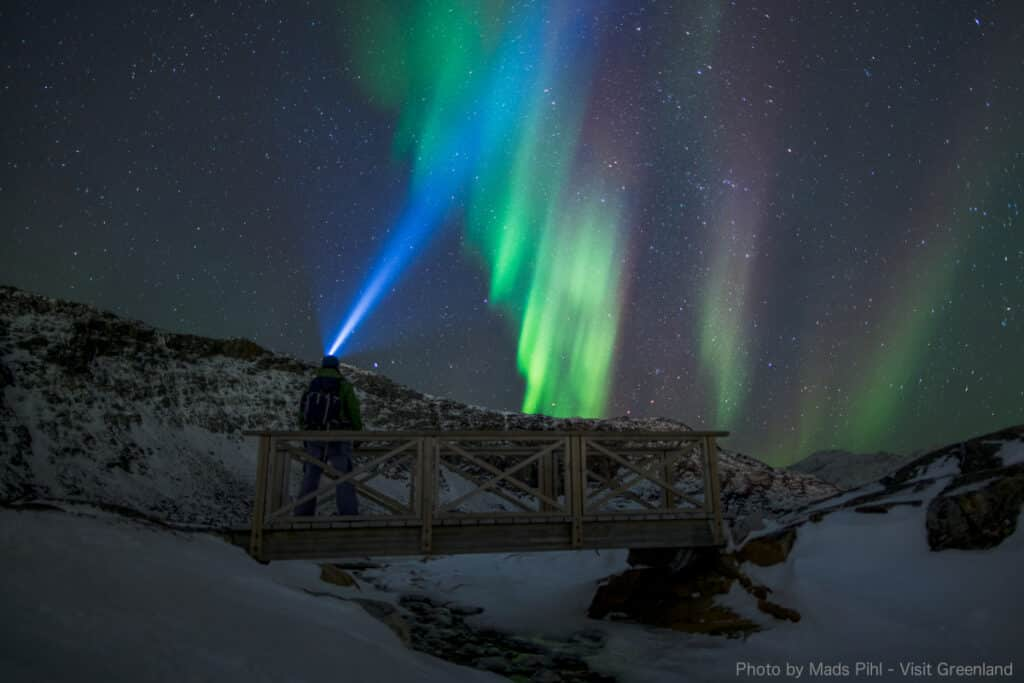 Hiker wearing a head torch looking at the northern lights in Greenland