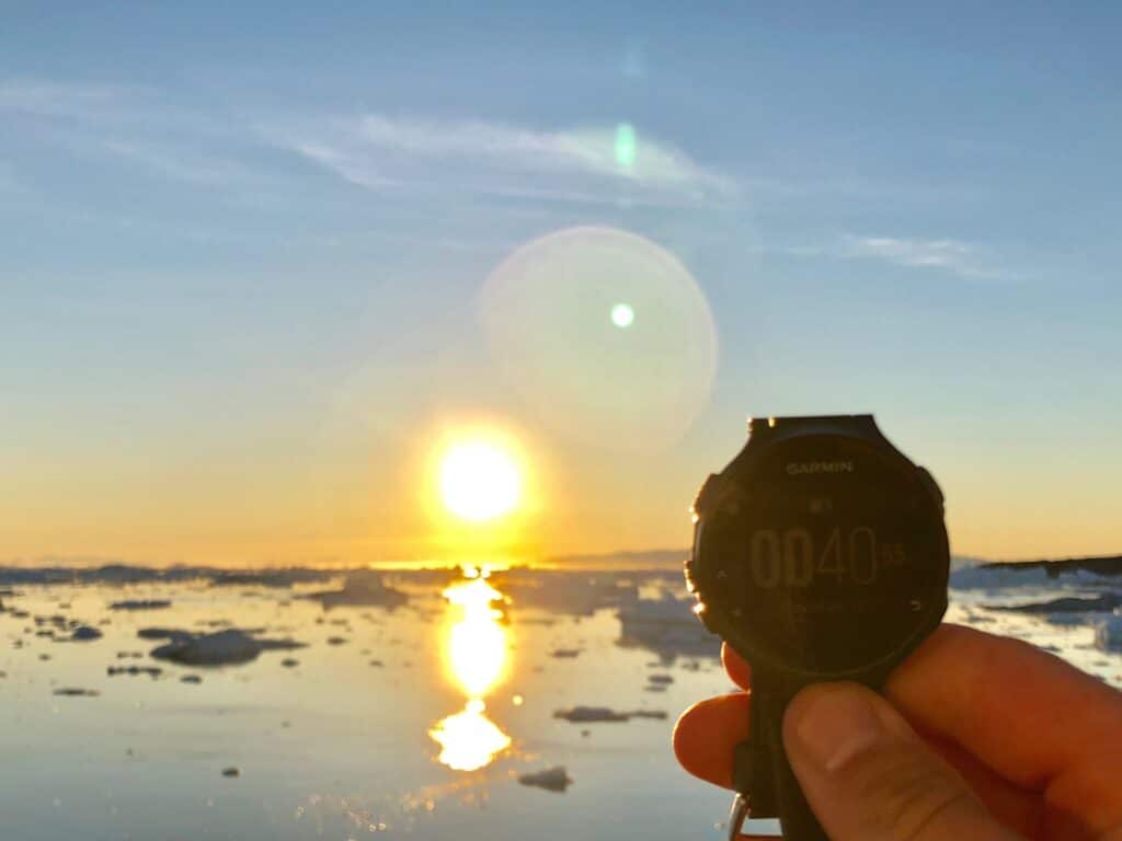 A watch being held up next to the midnight sun