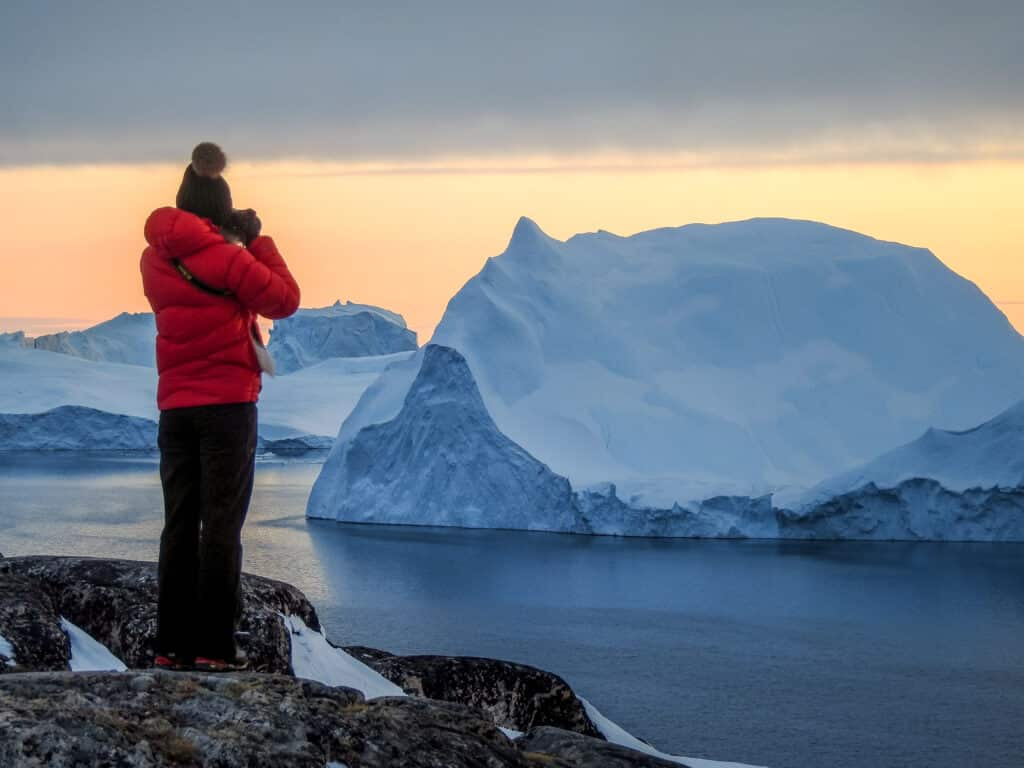 Woman taking pictures of enormous icebergs in the fjord