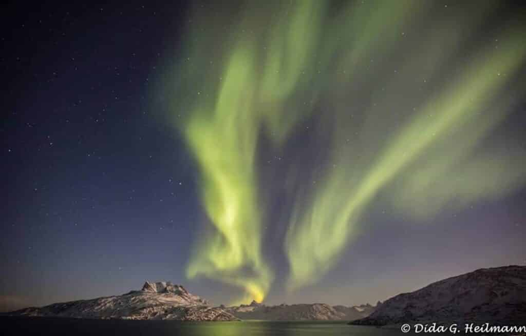 Northern lights over snow covered mountains