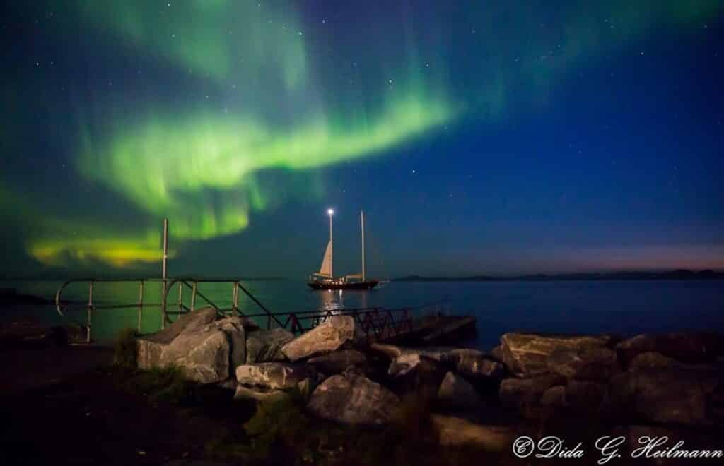 Northern lights dancing over a boat in the fjord