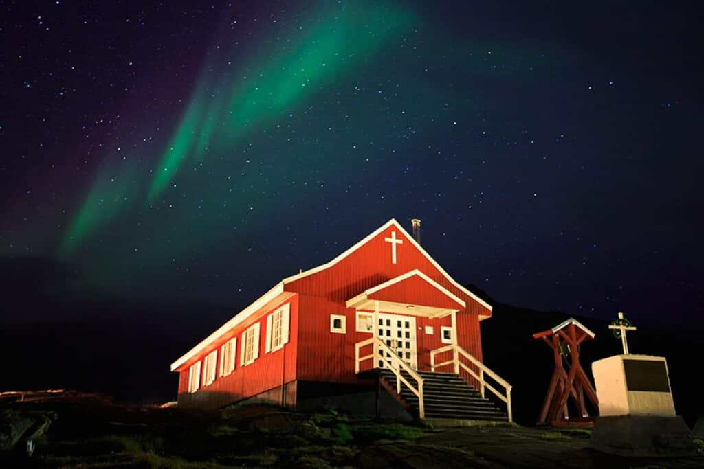 Northern lights over a small church in Greenland