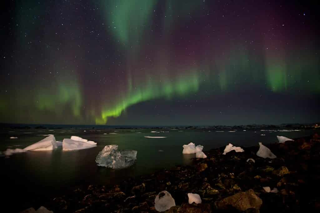 Green and purple northern lights over the icefjord in Greenland