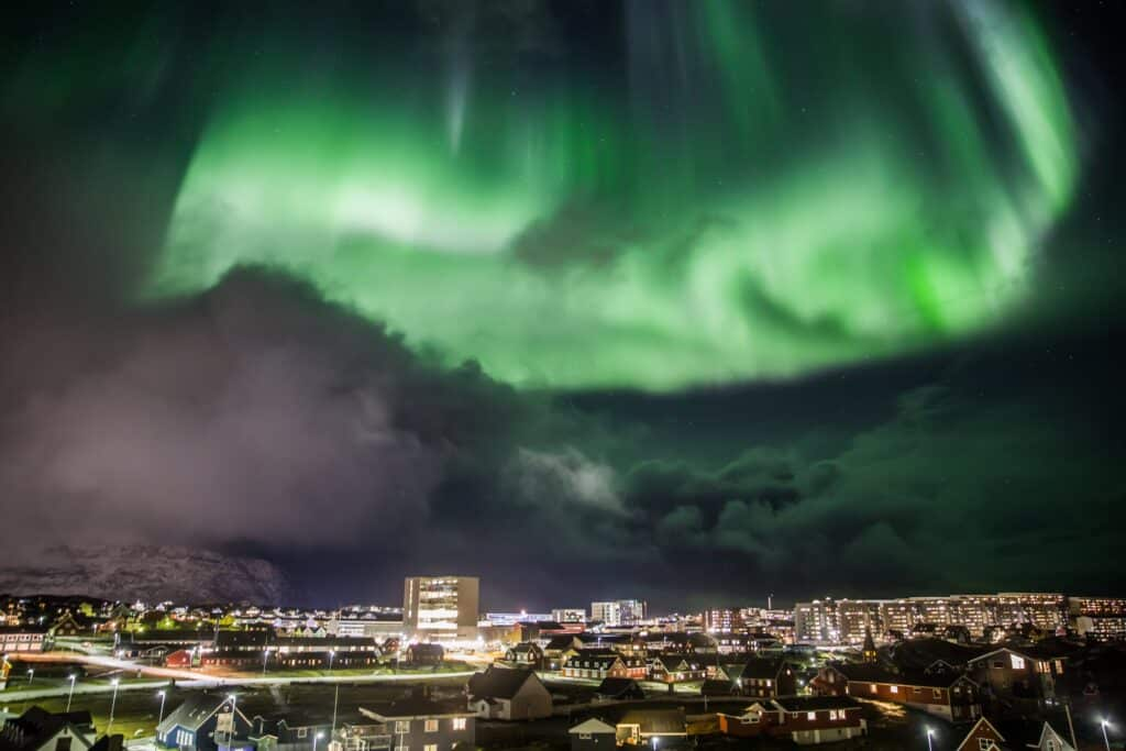 Northern lights on a cloudy evening over the centre of Nuuk city - winter - Guide to Greenland