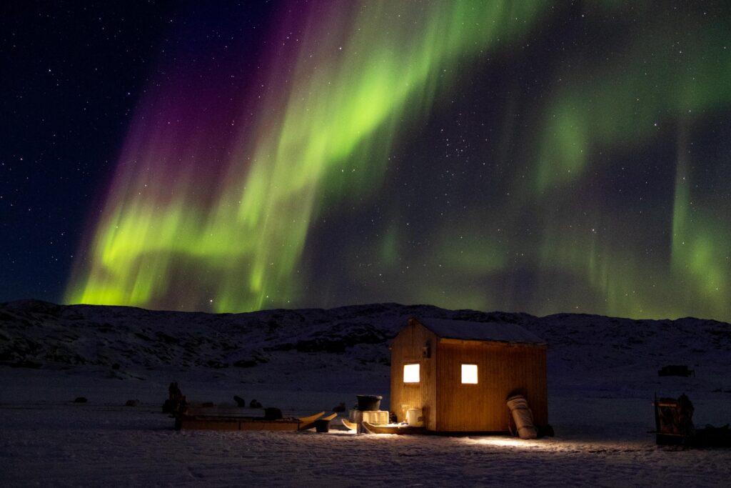 Northern lights colored purple and green over a small hut near Uummannatsiaq near Uummannaq