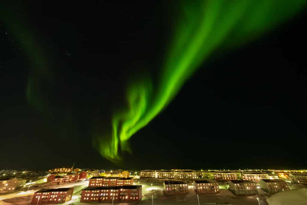 Northern Lights over red apartment buildings in Nuuk, capital of Greenland