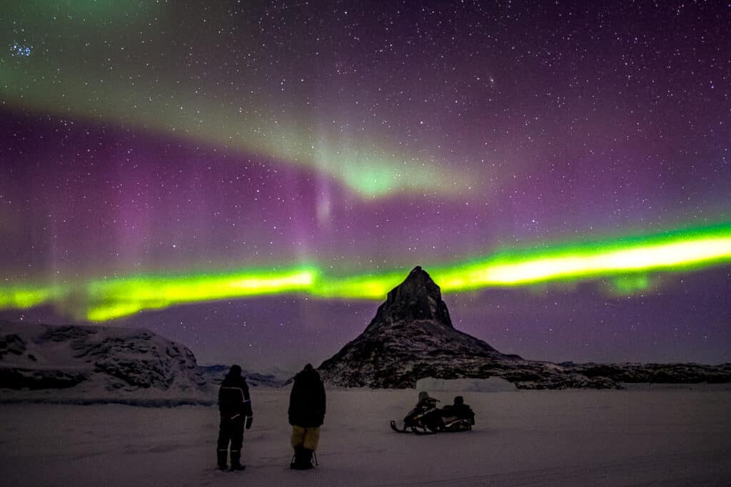 Couple on snowmobile tour looking at the northern lights in Greenland
