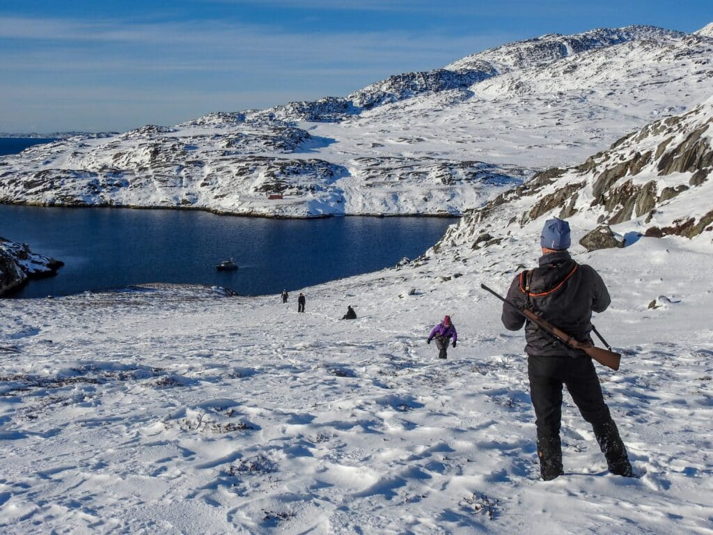 Man with riffle looking down to the fiord