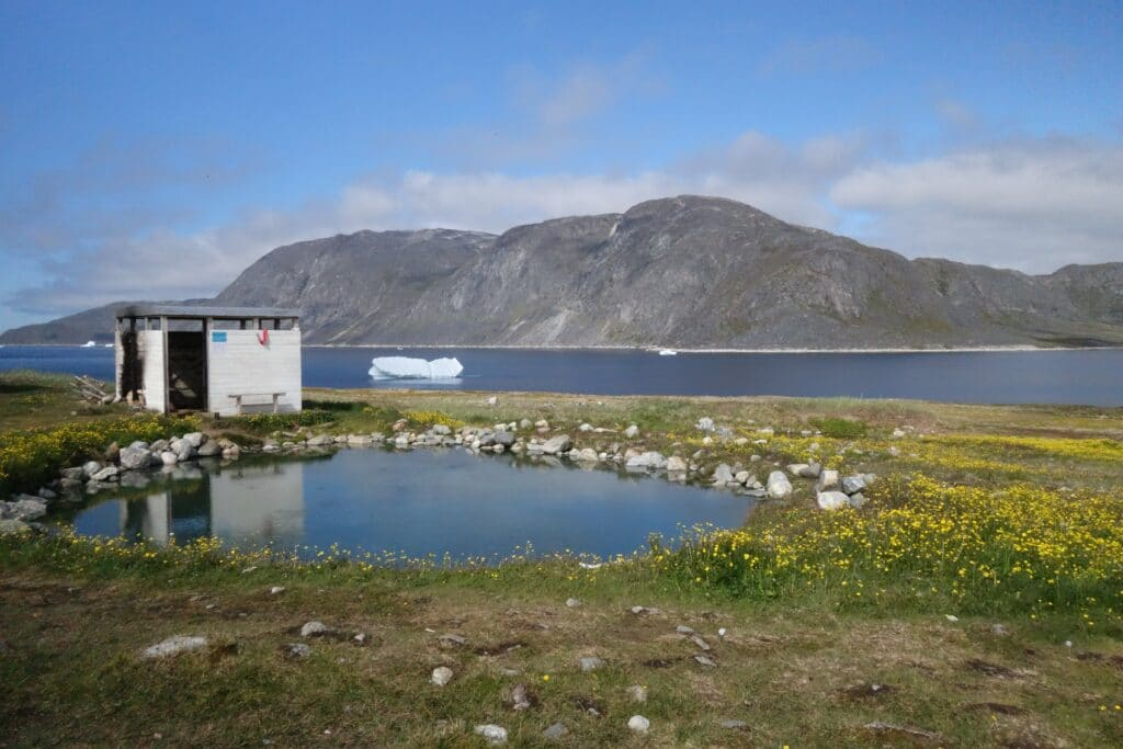 Small shelter next to a hot spring and an iceberg in the fjord