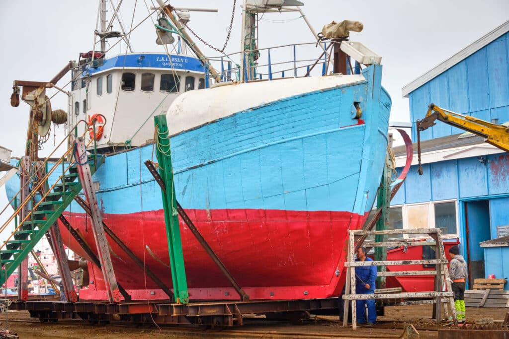 Blue and red ship at repair station in Aasiaat harbor
